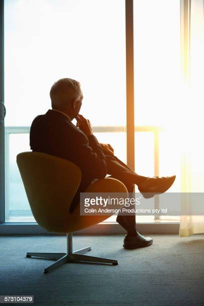 Older Caucasian businessman looking out window