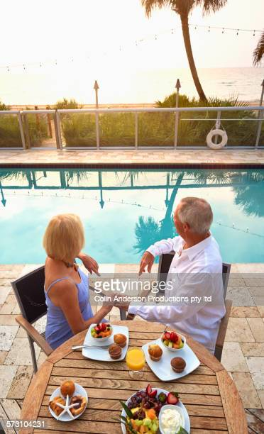 Older Caucasian couple at table near swimming pool