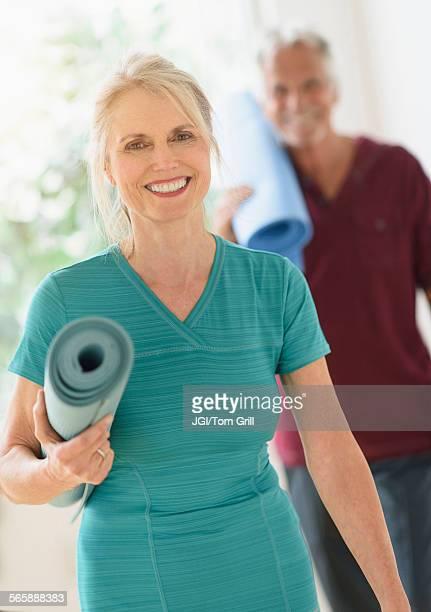 Older Caucasian couple carrying yoga mats