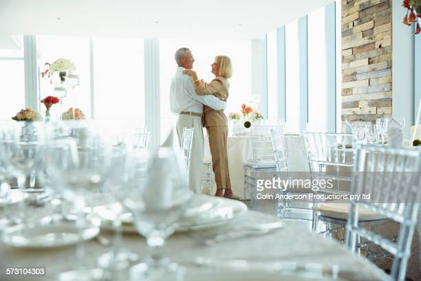 Older Caucasian couple dancing in dining room