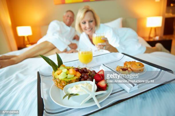 Older Caucasian couple eating breakfast on hotel room bed