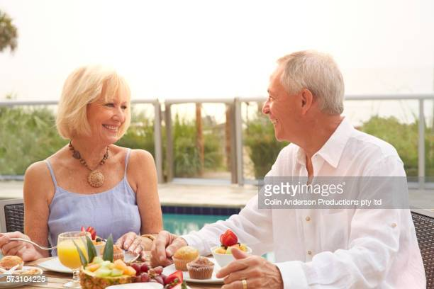 Older Caucasian couple eating near swimming pool