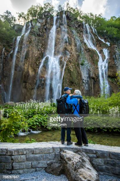 Older Caucasian couple hugging near waterfall