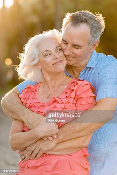Older Caucasian couple hugging on beach