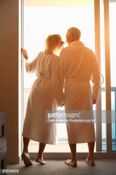Older Caucasian couple in bathrobes at balcony window