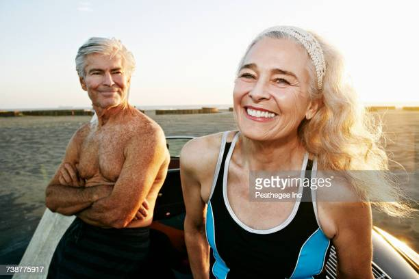 Older Caucasian couple leaning on convertible car at beach