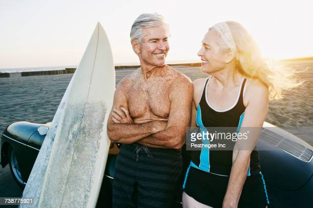 Older Caucasian couple leaning on convertible car with surfboards