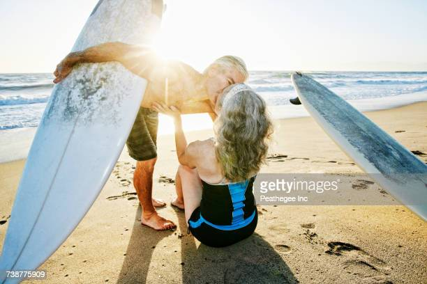 Older Caucasian couple on beach with surfboards kissing