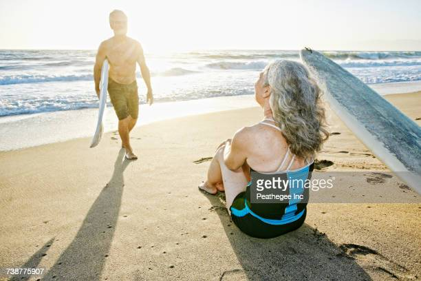 Older Caucasian couple on beach with surfboards