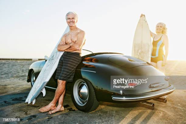Older Caucasian couple on standing near convertible car with surfboards