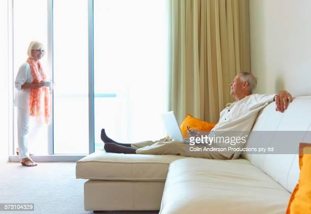 Older Caucasian couple relaxing in hotel room
