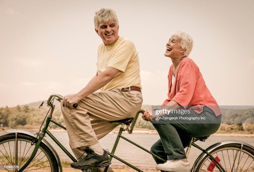 Older Caucasian couple riding tandem bicycle