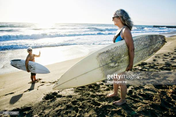 Older Caucasian couple standing on beach with surfboards