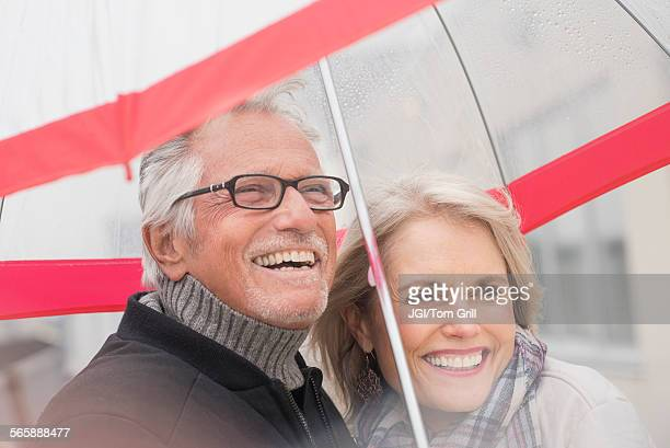 Older Caucasian couple standing under umbrella