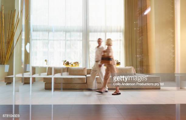 Older Caucasian couple walking in hotel lobby