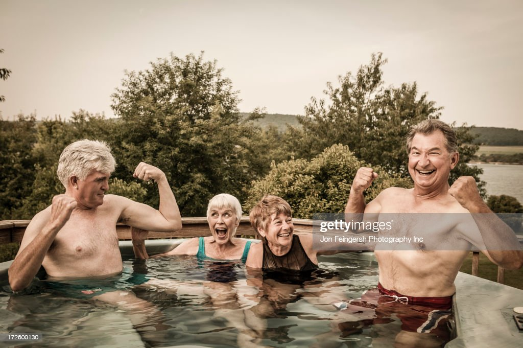 Older Caucasian couples relaxing in swimming pool