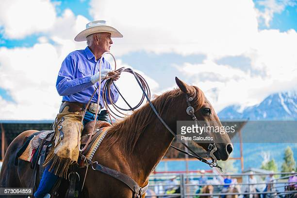 Older Caucasian cowboy riding horse at rodeo