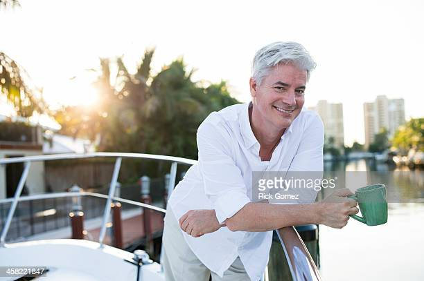 Older Caucasian having coffee on boat deck