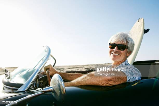Older Caucasian man in convertible car with surfboard on beach