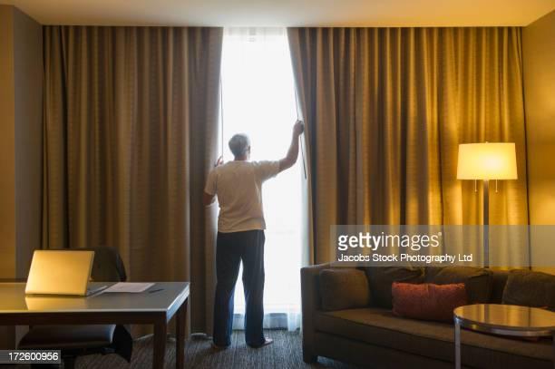 Older Caucasian man opening hotel curtains