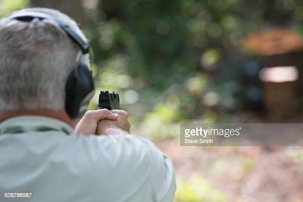 Older Caucasian man practicing with gun at shooting range