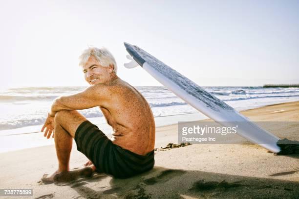 Older Caucasian man sitting on beach with surfboard