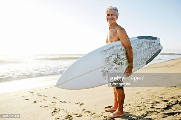 Older Caucasian man standing on beach carrying surfboard