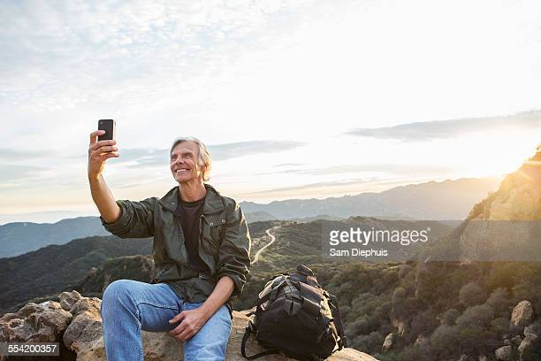 Older Caucasian man taking cell phone photograph on rocky hilltop