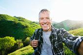Older Caucasian man taking selfie on rural hilltop