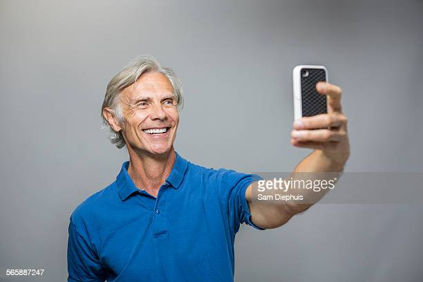 Older Caucasian man taking selfie