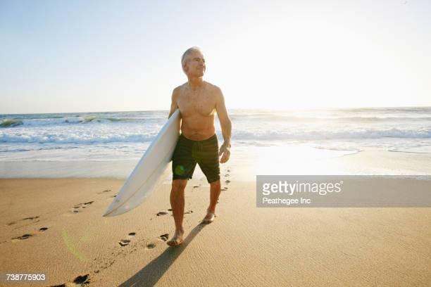 Older Caucasian man walking on beach carrying surfboard