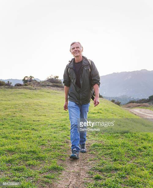 Older Caucasian man walking on dirt trail