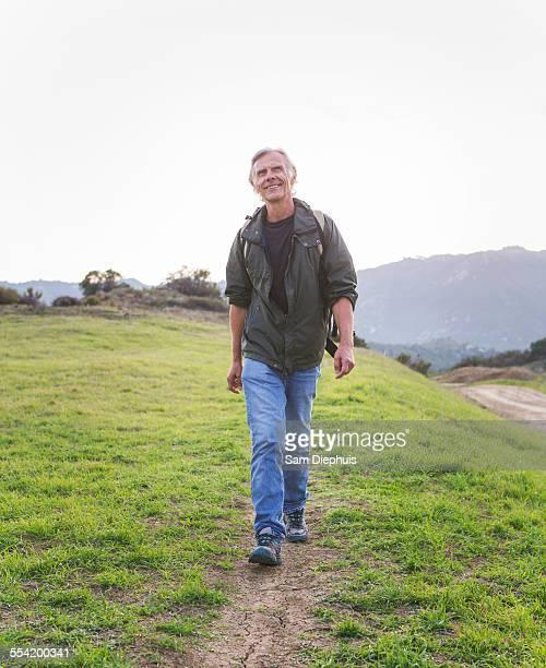 Older Caucasian man walking on dirt trail