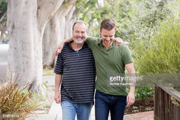 Older Caucasian man walking with son outdoors