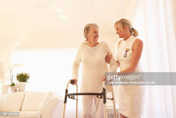 Older Caucasian woman and caregiver using walker