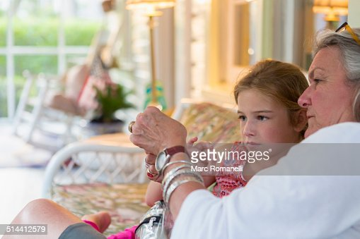 Older Caucasian woman and granddaughter using cell phone together