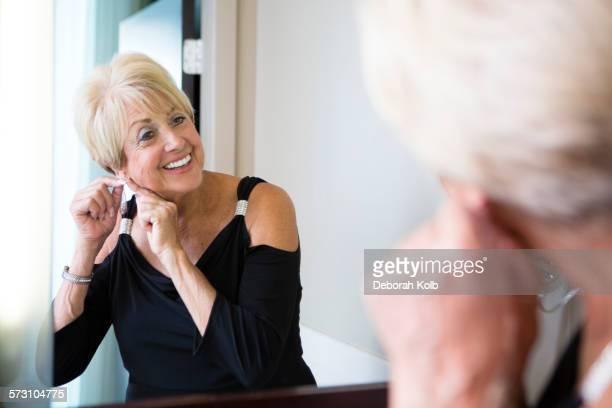Older Caucasian woman attaching earring in mirror