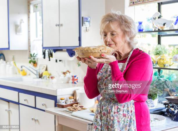 Older Caucasian woman baking pie in kitchen