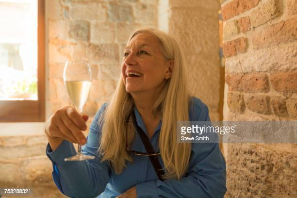 Older Caucasian woman drinking white wine