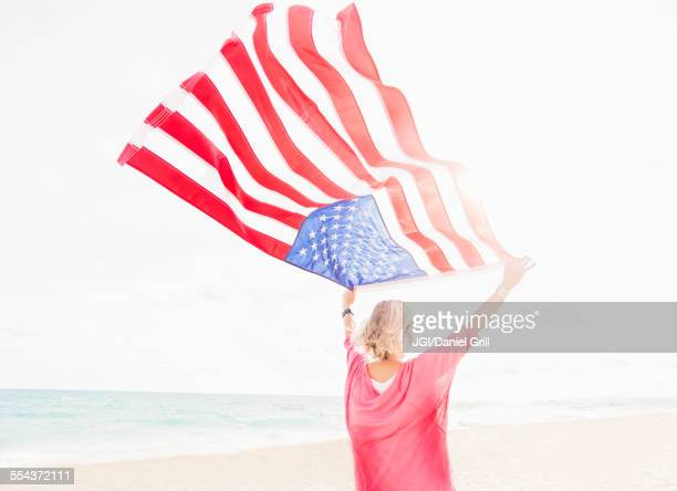 Older Caucasian woman holding American flag on beach