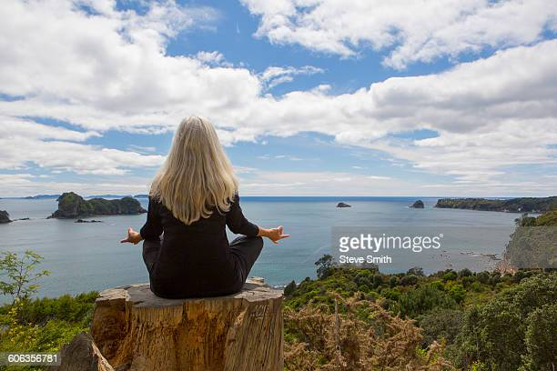 Older Caucasian woman meditating on cliff near ocean