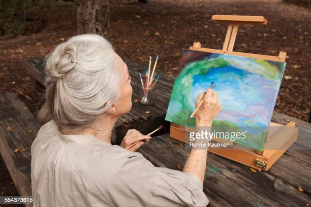 Older Caucasian woman painting in park