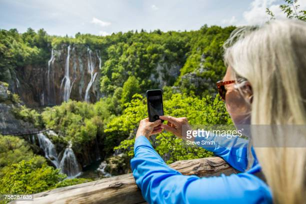 Older Caucasian woman photographing waterfalls with cell phone
