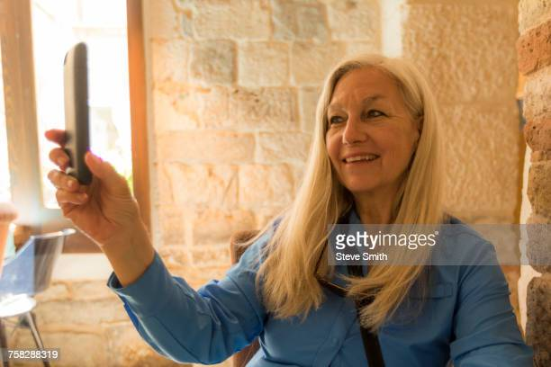 Older Caucasian woman posing for cell phone selfie