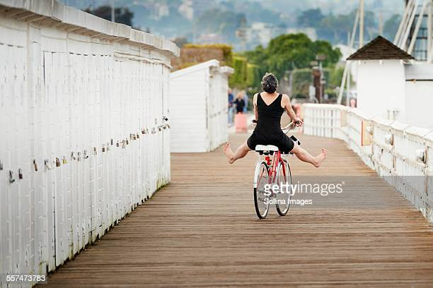 Older Caucasian woman riding bicycle on wooden dock