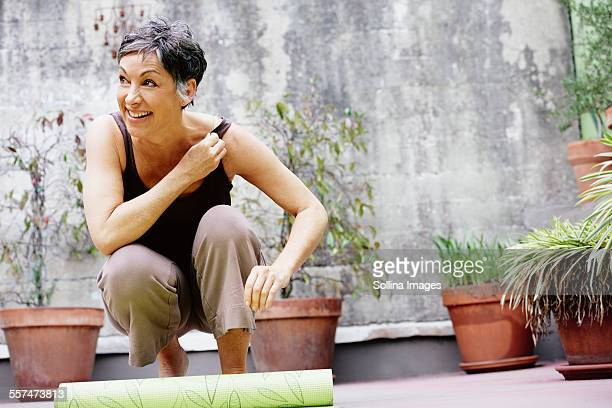 Older Caucasian woman rolling up yoga mat in courtyard