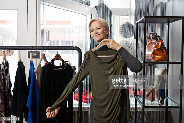 Older Caucasian woman shopping in clothing store