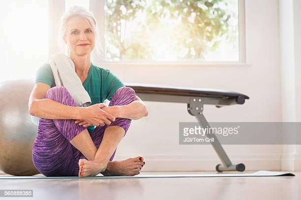 Older Caucasian woman sitting on gym floor