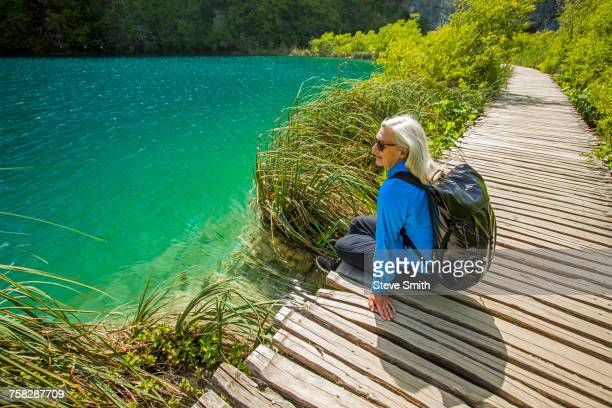 Older Caucasian woman sitting on wooden pathway near water