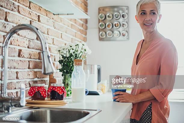 Older Caucasian woman stirring coffee in kitchen